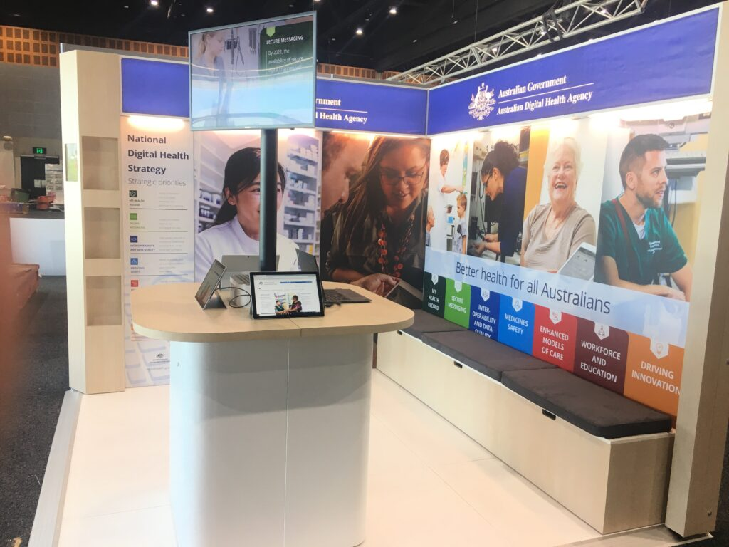 Modular travelling exhibition stand with raised floor, backlit fabric graphics, bench seating with storage and custom counter with telescopic TV stand.