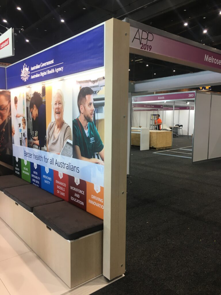 Back wall of exhibition stand with graphics and bench seating with storage.