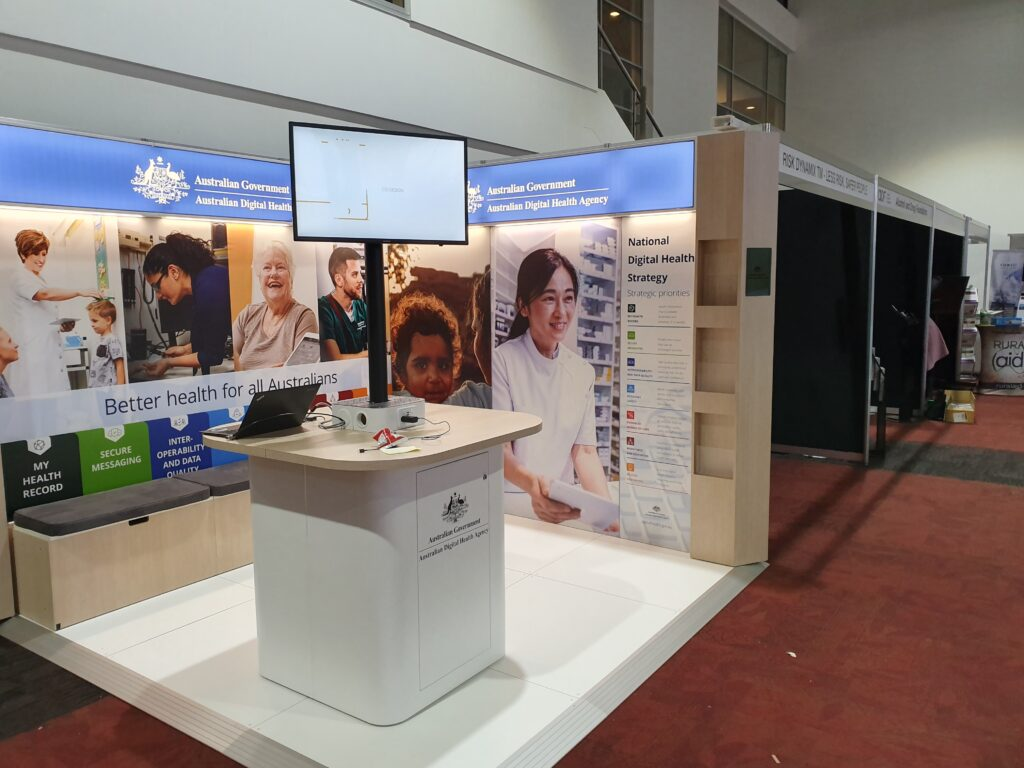 Modular travelling exhibition stand with raised floor, backlit fabric graphics and custom counter with telescopic TV stand.