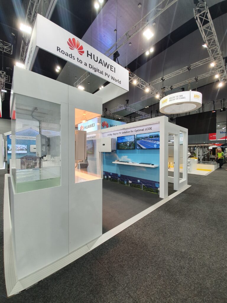 Custom made product display cases on custom exhibition stand with overhead rigging and wall mounted LCD screens.
