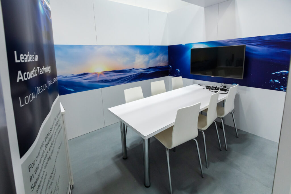 Boardroom on custom exhibition stand with wall graphics and wall mounted LCD Screen