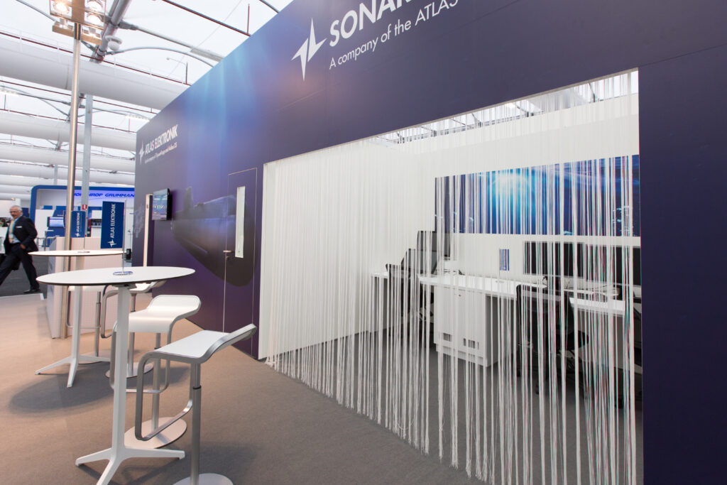 Custom exhibition stand with large format graphics, raised carpeted exhibition floor, white stools and bar tables.