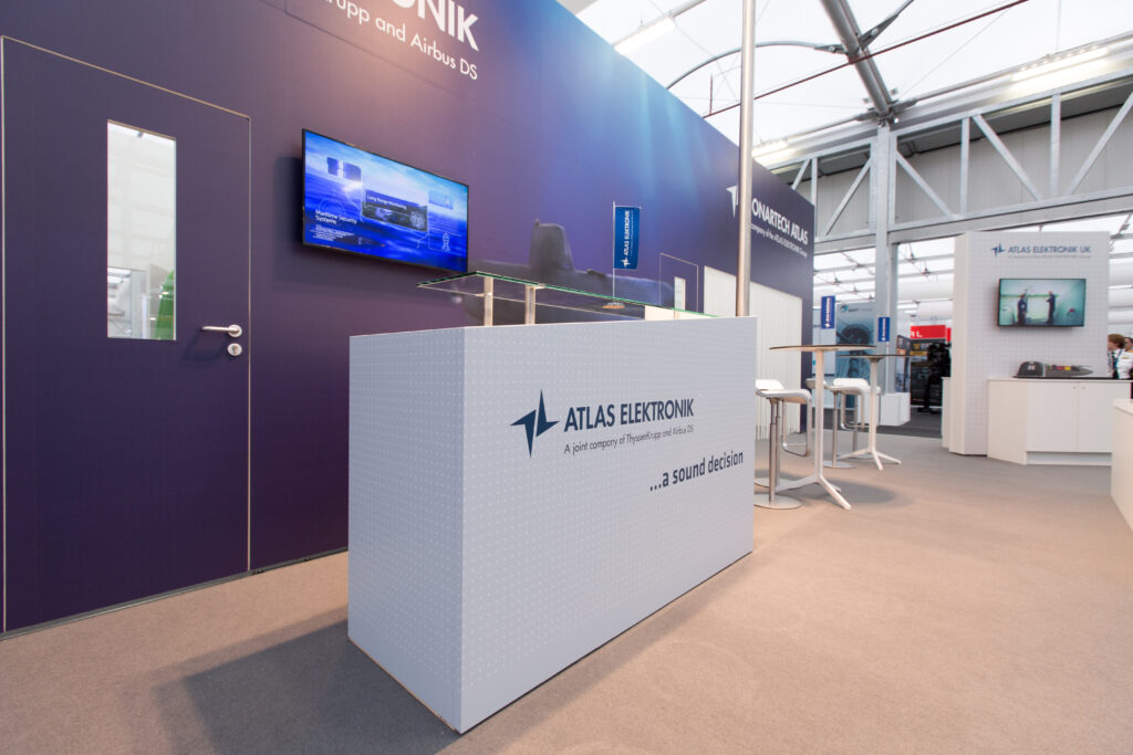 Custom reception counter with full graphic wrap on custom exhibition stand.